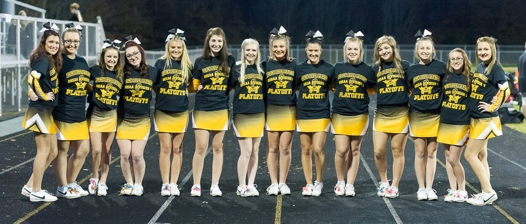 cheerleaders wearing yellow skirts and black shirts standing on track