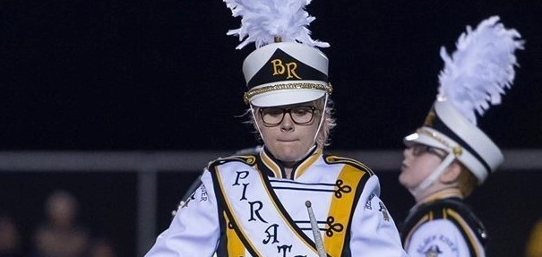 one band member pounding the drum during game