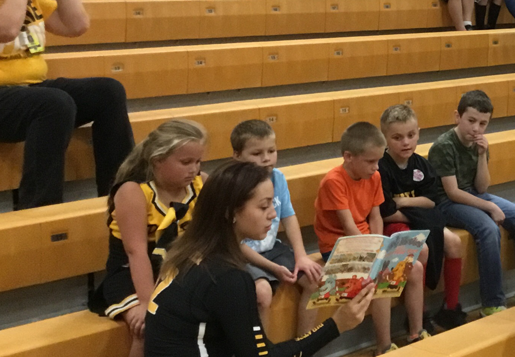 Senior athletes reading to second graders
